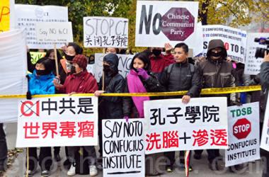 2014年、カナダのトロントで、孔子学院に反対の意を示すプラカードを掲げる市民(大紀元)