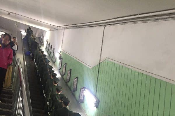 19大前、北京市内の地下鉄駅で整列してエレベーターに乗る軍人