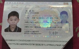 天津国際空港で出国の際、はさみを入れられた包龍軍氏の長男のパスポート。(包龍軍氏のフェイスブックより)