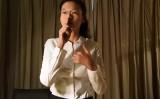 李氏の妻は、面会で盗聴器を装着されていると意味する夫の動きを再現した。(中央社)