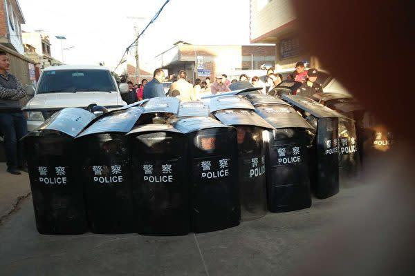 雲南省に発生した大規模な抗議活動で、盾で警戒に当たっている警察隊。(ネット写真)
