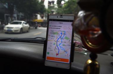 写真は2016年5月13日、中国のタクシー運転手が広西省桂林市の街で、運行中に滴滴出行のGPS機能を使っている場面(GREG BAKER/AFP/Getty Images)