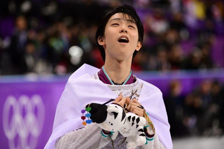 右足首靭帯損傷というケガから4カ月、満身創痍で臨んだ羽生結弦。平昌オリンピック8日目フィギュアスケート17日目、フリープログラムを終え、前日のショートプログラムと合わせて合計300点以上を獲得し、金メダルが決まった。日の丸をまとい氷上を滑る羽生結弦選手(ROBERTO SCHMIDT/AFP/Getty Images)