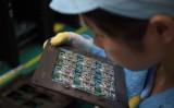 写真は、広東省東莞市にある携帯電話用半導体メーカーの労働者(NICOLAS ASFOURI/AFP/Getty Images)