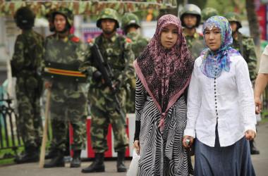 2009年、新疆ウイグル自治区で撮影。中国武装警察を背景に立つウイグル族の女性2人(PETER PARKS/AFP/Getty Images)