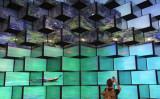 ドイツのベルリンで2014年9月に開かれたIFA家電展示会で、LEDテレビを撮影する男性。参考写真 (Sean Gallup/Getty Images)