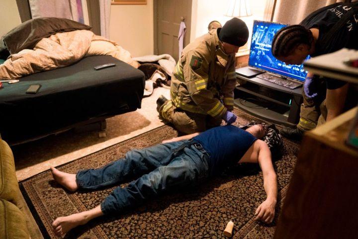 4月、ニューハンプシャー州でヘロイン摂取により意識を失った男性を救護する消防士たち(DON EMMERT/AFP/Getty Images)