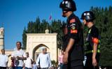 写真は2017年6月撮影。新疆ウイグル自治区カシュガル市でイスラム教モスクから出たイスラム教徒と警戒に当たる警官らの様子(JOHANNES EISELE / AFP / Getty Images)