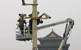 独メディアによると、中国当局は一部のドイツ系企業を「社会信用システム」のブラックリストに入れた。写真は、ある一人の労働者が北京市で監視カメラを設置している様子(Guang Niu/Getty Images)