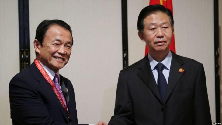 日中財務対話で、麻生太郎・副総理兼財務大臣、中国の劉昆・財政部長(財務相)が握手をかわす(KOJI SASAHARA/AFP/Getty Images)
