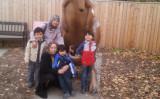 ウイグル族でカナダ在住ラビヤ・ムハンマドさんは、2018年2月から4カ月間、新疆ウイグル自治区で母親(65)が拘留されたと述べた。写真は、カナダ旅行の母親を迎えたラビヤさんと子供たち(提供写真)
