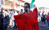「移民はいいが不法移民はダメ」と書かれたプラカードを持つ男性(Charlotte Cuthbertson/The Epoch Times)