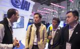 2016年1月、テルアビブで開かれたサイバー技術展示会で、イスラエルの宇宙開発企業IAIの説明に聞き入る、シンガポールからの華人ビジネスマン(記事にある企業、人物ではありません JACK GUEZ/AFP/Getty Images)