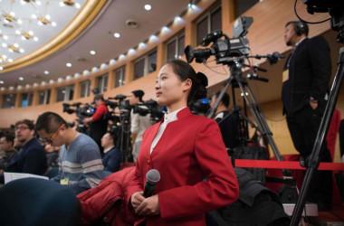 2018年3月、中国人民大会堂で開かれた会議でマイクを手にする女性アナウンサー(NICOLAS ASFOURI/AFP/Getty Images)