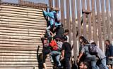 11月25日メキシコの国境ティファナで、米国側へ柵を超えて違法に入国しようとする移民たち(Charlotte Cuthbertson/The Epoch Times)