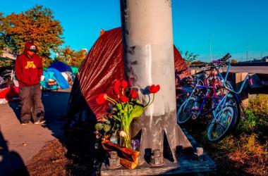 2018年10月、米ミネソタ州ミネアポリスのある町の鉄塔のもとに花が飾られている。死亡したホームレスは、オピオイド中毒者で働くこともできず路傍で絶命した(KEREM YUCEL/AFP/Getty Images)