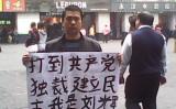 写真は2013年2月13日撮影。中国南部広東省広州市繁華街で、民主化運動活動家の劉輝さんが「打倒共産党独裁」とのプラカードを持って、国内憲政民主の確立を呼び掛けた(情報提供者より)