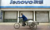 シャッターの閉まったレノボ店舗の前を通過する自転車に乗った男性。2004年12月、北京で撮影(FREDERIC J. BROWN/AFP/Getty Images)