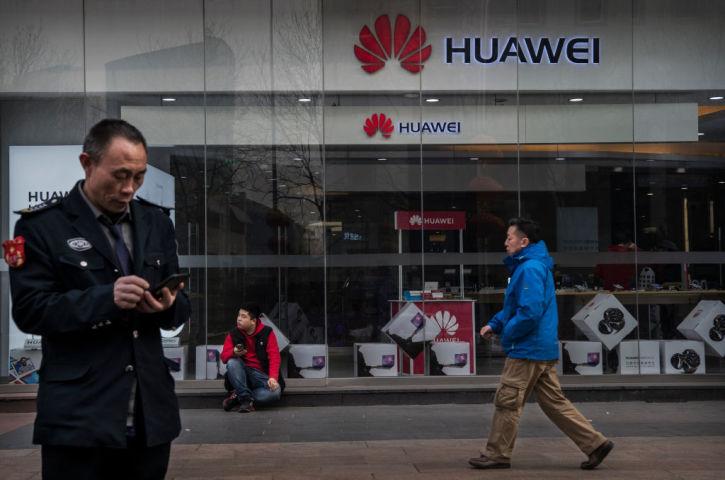 2019年1月、北京のファーウェイ(華為科技、HUAWEI)店舗前でスマートフォンを操作する男性(Kevin Frayer/Getty Images)