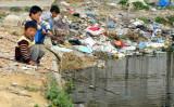 プラスチックごみの堆積する河で、釣り遊びをしている子供たち、上海で2004年撮影(LIU JIN/AFP/Getty Images)