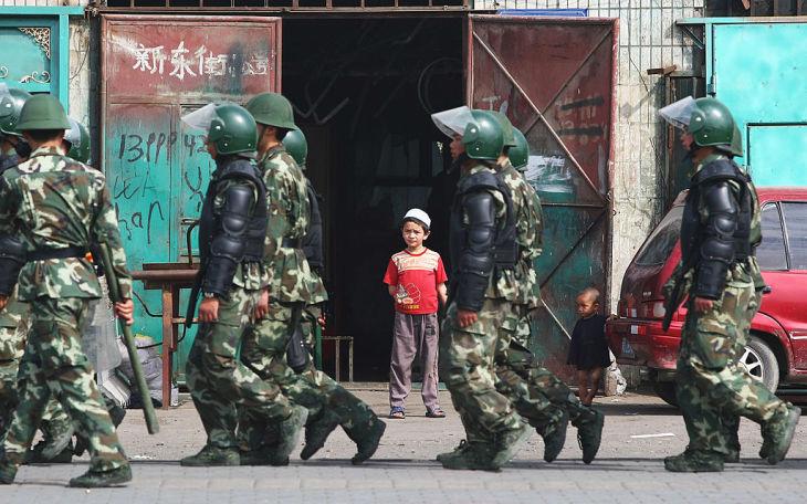 2009年、新疆ウイグル自治区ウルムチで、中国軍兵士が横切るのを見つめる少年(Guang Niu/Getty Images)
