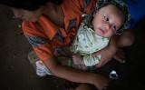 ミャンマーのカチン州難民キャンプ近くのキリスト教会で、赤ちゃんを抱える若い女性(Lauren DeCicca/Getty Images)