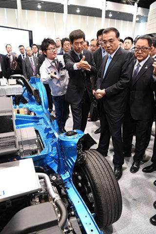 昨年5月、トヨタ自動車北海道の工場を視察した中国の李克強首相(左から2番目)とトヨタ自動車の豊田章男社長(左から1番目)(JIJI PRESS/AFP/Getty Images)