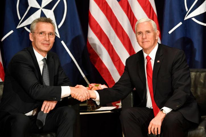 2019年2月、ミュンヘン安全保障会議で握手を交わす米ペンス副大統領とストルテンベルグNATO事務総長(THOMAS KIENZLE/AFP/Getty Images)