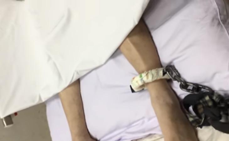 ひん死の状態でも、ベッドと足を鎖で縛られる法輪功学習者(于溟さん撮影)