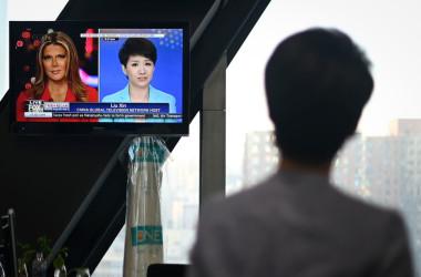 CGTN記者の劉欣氏(後ろ姿)は、30日のFOXニュース出演番組を確認している(WANG ZHAO/AFP/Getty Images)