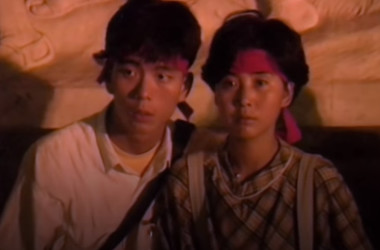 六四天安門事件で、自由を象徴する像の前に座る若いカップル。広場の拡声器から放送されている政府声明を聞いている(Screen Shot)