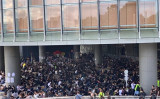 香港の大学生らは21日午前7時から、黒いTシャツをまとい、香港島・金鍾(アドミラリティ)にある政府総部の庁舎前に集まり座り込みを始めた(李逸/大紀元)