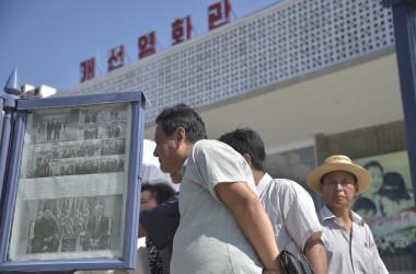 7月1日、トランプ大統領と金委員長の軍事境界線・板門店での前日の会談を報道した労働新聞と、平壌市内に掲げられた同紙を読んでいる平壌市民(GettyImages)