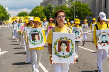 法輪功学習者は中国当局の迫害を受けて亡くなった学習者の遺影を掲げてパレードを行進した(Mark Zou/大紀元)