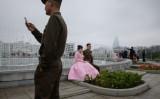 中国通信技術大手ファーウェイは、北朝鮮の厳格な情報システム構築に協力しているという。米シンクタンク傘下の北朝鮮情報サイト・38ノースが7月22日報じた。写真は2019年4月、平壌市内で、記念撮影するカップルと携帯電話を操作する若い兵士(GettyImages)