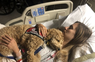 Katie Harris in the hospital with her service dog Moxie. (Courtesy of Katie Harris)