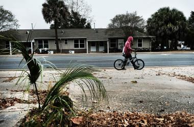 米フロリダ州ペンサコラにある住宅街で、自転車を持って歩いている男性。2016年12月4日撮影。(Spencer Platt/Getty Images)