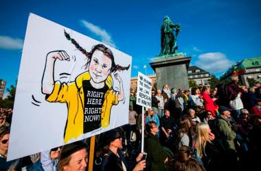 グレタさんを国連に出した環境団体、中国政府の代理人の疑いがあると米委員会に指摘されている。写真は9月27日、スウェーデンのストックホルムで行われた環境活動家によるパレードで、グレタさんの似顔絵が描かれたパネルを掲げる参加者(GettyImages)