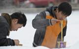 クレディ・スイスの中国人エコノミストは、中国国内の即席麺販売の回復は消費者の節約志向を反映したと指摘。写真は雪が降る日、観光客2人が北京市天安門広場でインスタント麺を食べている様子(LIU JIN/AFP/Getty Images)