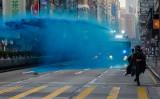 10月20日に行われた香港大型デモで、化学物質の含まれる青い水を発射する警察車両と、逃げるデモ参加者(GettyImages)