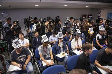 11月4日、香港警察の記者会見で各報道機関の記者6人がヘルメットを着けて、警察の暴力と記者の拘束を抗議した(余鋼/大紀元)