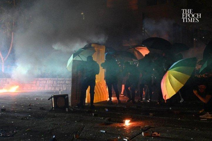 自動小銃やスタングレネードを装備する香港警察に立ち向かう、若いデモ隊。11月17日夜、理工大学で撮影(大紀元)