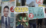 11月24日、香港屯門区の投票所の前で、市民は民主派候補者の盧俊宇氏への投票を呼び掛けた(余天佑/大紀元)