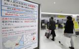 成田空港で新型コロナウイルスについて注意喚起を行っている(STR/JIJI PRESS/AFP via Getty Images)