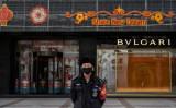 2020年2月18日、中国北京の商店街で、中国人警備員が防護マスクをして立っている(Kevin Frayer/Getty Images)