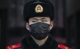 中国北京火車駅にいるマスク着用の警官。1月22日撮影(Kevin Frayer/Getty Images)