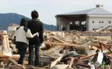 2011年3月19日、岩手県陸前高田市で、大地震と津波を受けて倒壊した建物を見つめる若い姉弟(GettyImages)