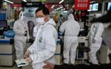 3月30日、武漢市内の薬局で防護服を付けて接客する従業員(GettyImages)