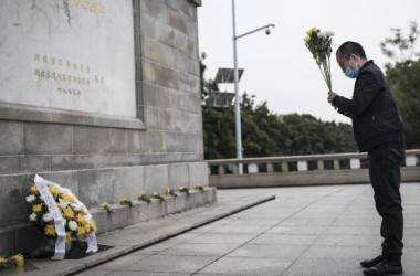 2020年4月4日に中国武漢で、中共ウイルスによって亡くなった人々に花を供える住民(Getty Images)