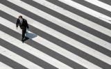 緊急事態宣言が発令され、人通りの少ない交差点を渡る男性。東京・銀座で4月28日撮影(GettyImages)